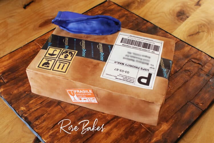 Back view of a cake shaped like and amazon cardboard shipping box and a blue zulily package.  The cake is sitting on a cake board that looks like wood made from fondant and hand painting.