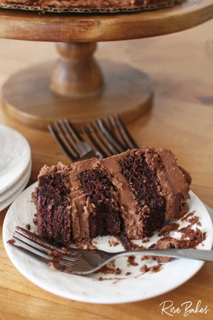 A slice of chocolate cake filled with chocolate frosting on a white plate.  A fork is resting on the plate and a couple of bites have been eaten from the slice of cake.  The wooden cake stand is in the background.