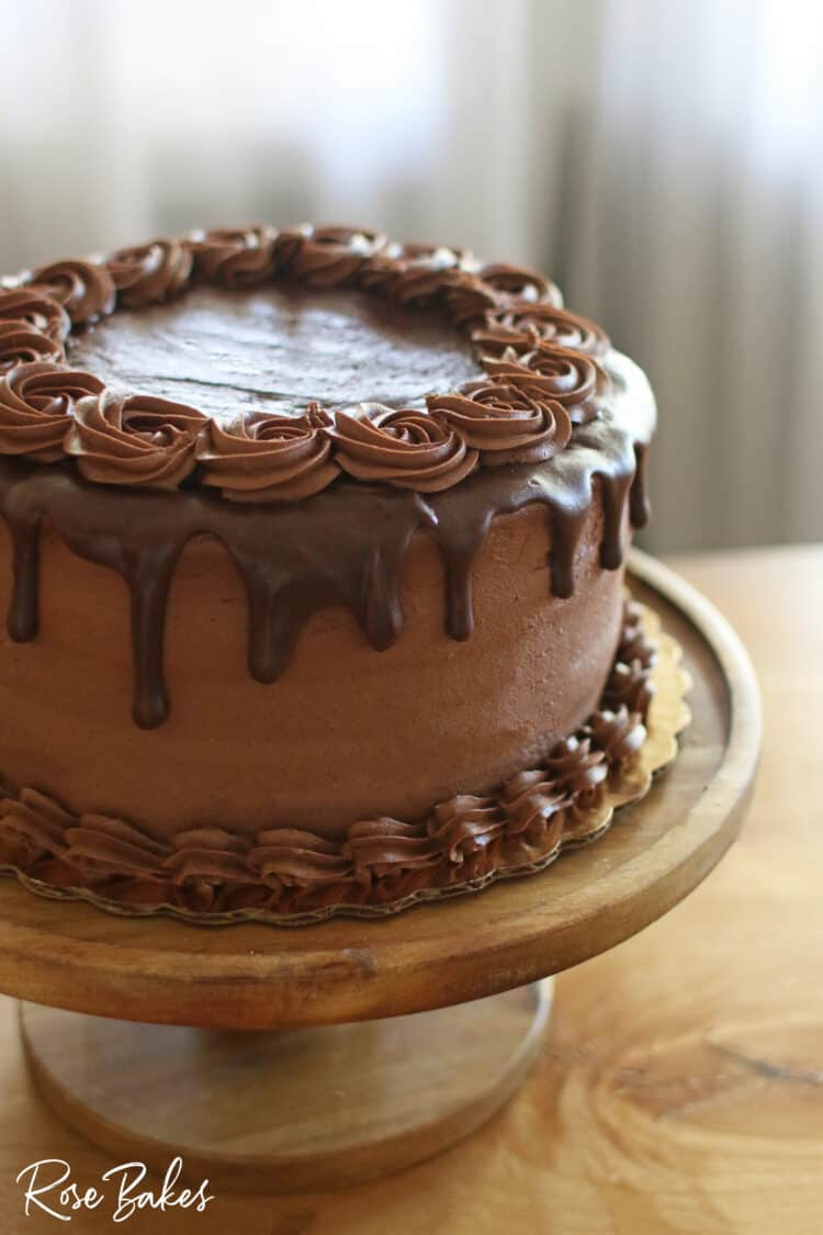 Chocolate Cake with chocolate drip and chocolate rosettes on top.  The cake is displayed on a wooden cake stand.