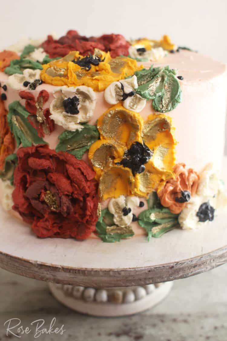 Close up view a cake frosted white with green leaves and red, yellow, and white buttercream flowers created with palette knives.  The cake is displayed on a rustic wood cake stand.