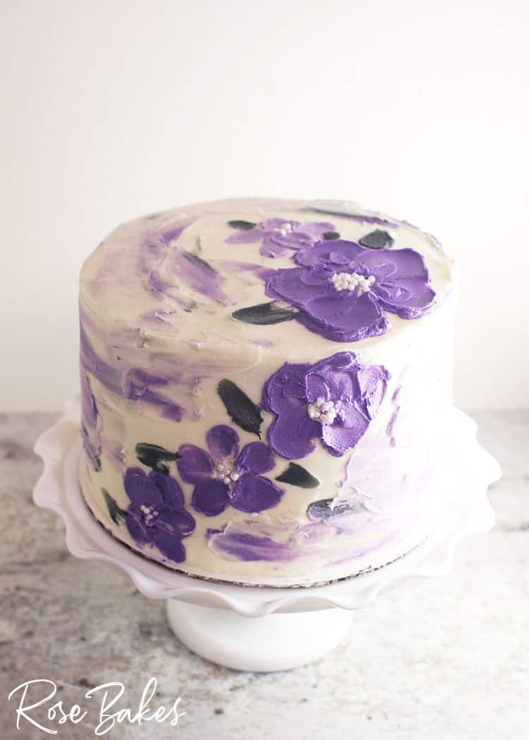 A white buttercream cake with purple watercolor streaks and purple flowers created with a palette knife and white sprinkles for the centers.  The cake is displayed on a white cake stand with a large ruffled edge.