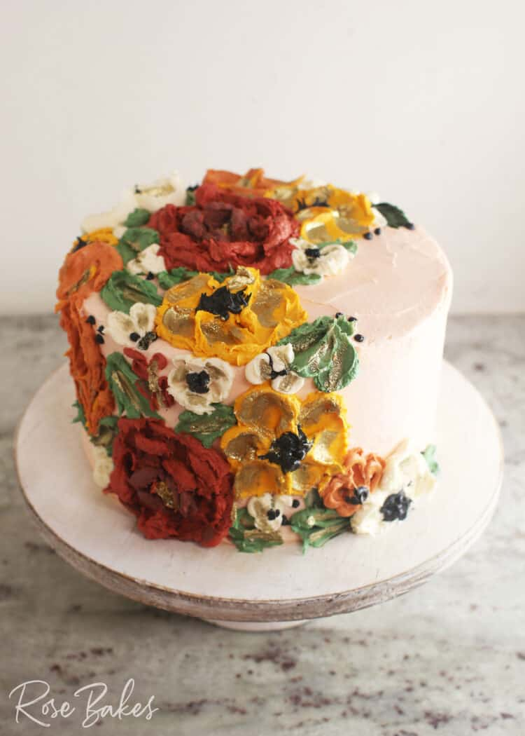 Cake frosted white with green leaves and red, yellow, and white buttercream flowers created with palette knives on one side of the top of the cake and cascading down the side of the cake.