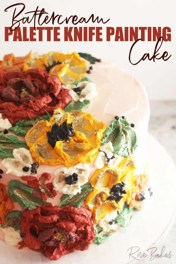 """Close up view a cake frosted white with green leaves and red, yellow, and white buttercream flowers created with palette knives.  The text at the top of the image reads, """"Buttercream Palette Knife Painting Cake"""""""