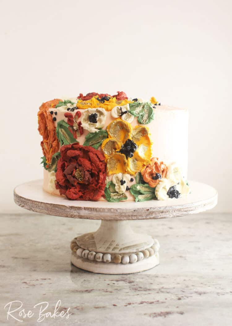 Front on view of a cake frosted white with green leaves and red, yellow, and white buttercream flowers created with palette knives on one side of the top of the cake and cascading down the side of the cake. The cake is displayed on a rustic wooden cake stand with a bead border around the base of the stand.