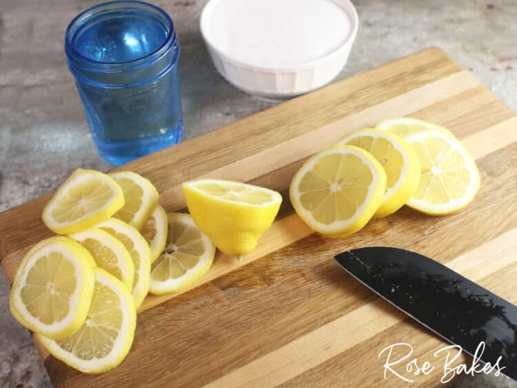 sliced lemons on a cutting board for candied lemons