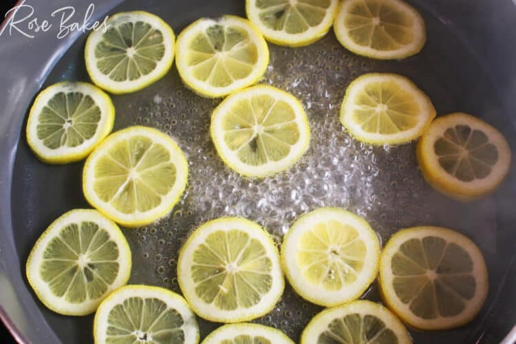 lemon slices in a shallow pan of sugar water that is boiling to make candied lemons