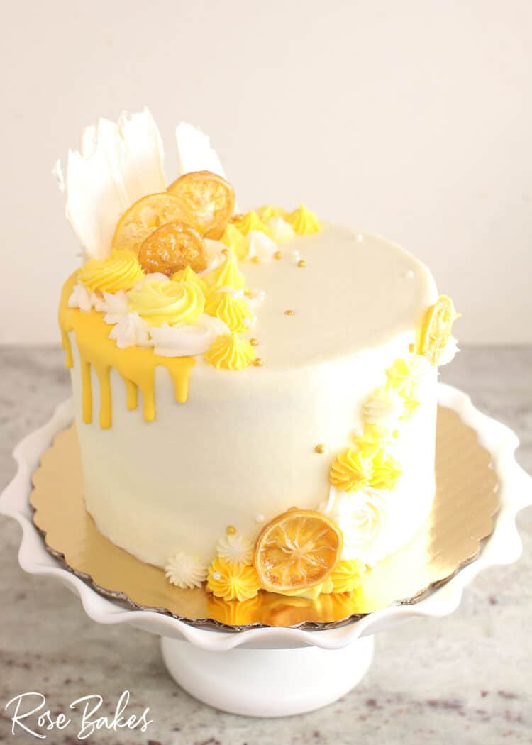 Cake frosted in white buttercream with yellow drip and yellow buttercream rosettes and stars around the top left and front right of the cake.  Among the buttercream decorations are candied lemons and white chocolate fans.  The cake is displayed on a white cake stand with a large ruffled edge.
