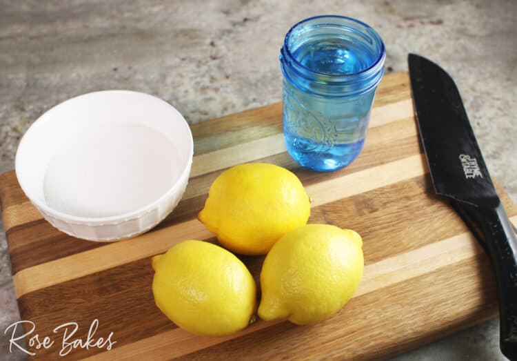 lemons, white bowl of sugar, blue cup of water and knife on a cutting board