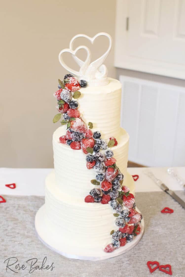 Three tiered wedding cake with textured buttercream and cascading sugared berries.  The topper is white interlocking hearts.