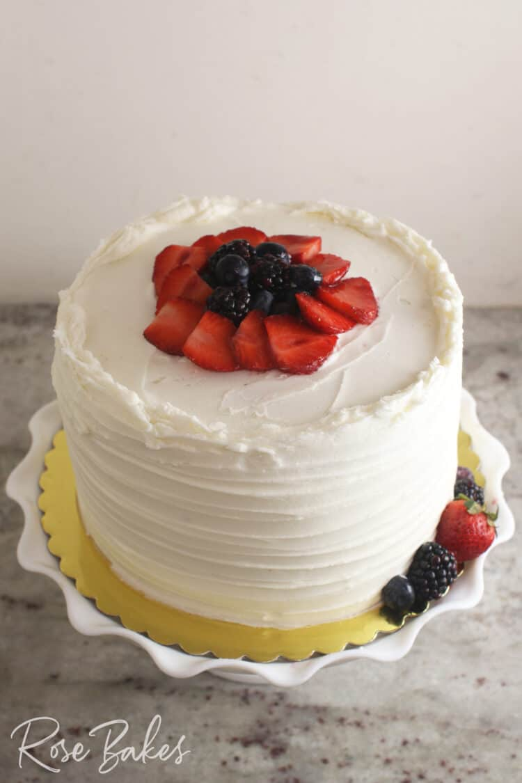 Chantilly Cake with sliced strawberries, blueberries, and blackberries on top. Displayed on a white ruffled cake stand.