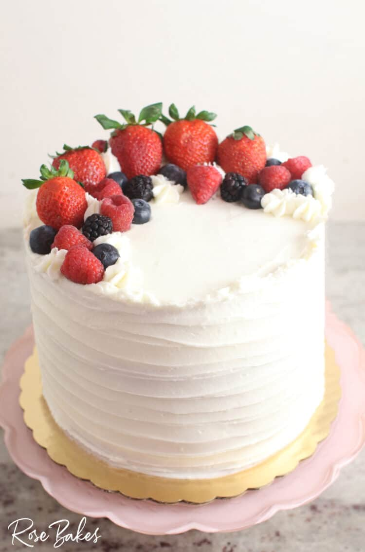 Chantilly Cake with fresh berries  Displayed on a light pink scalloped cake stand.
