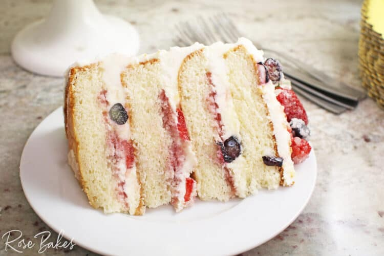 Slice of Chantilly Cake with berries in the filling and on top of the cake.  The cake is on a round white plate.