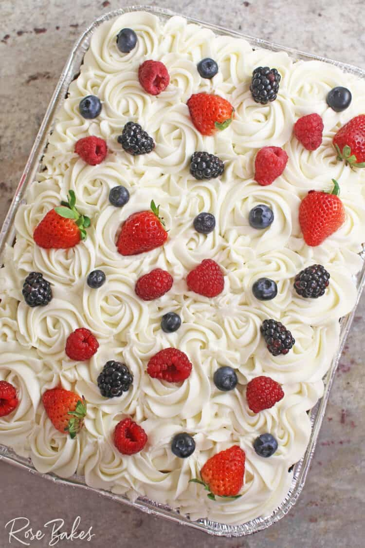 Chantilly Sheet Cake in a disposable pan. Cream Cheese frosting piped in rosettes and dotted with fresh berries on the top.