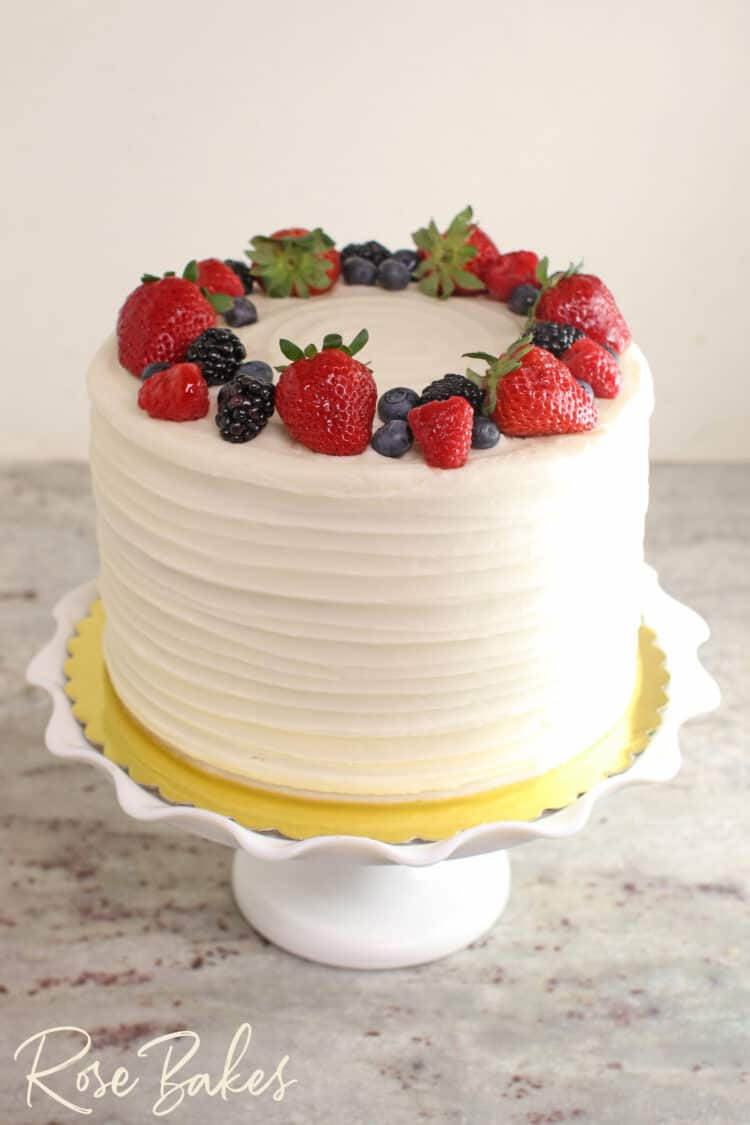 Chantilly Cake with a fresh berry wreath on top. Displayed on a white ruffled cake stand.