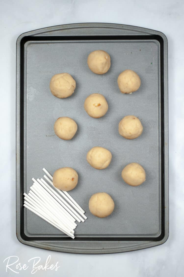 Cake pops rolled into balls on a baking sheet.  White pop sticks are in a stack at the bottom of the pan.
