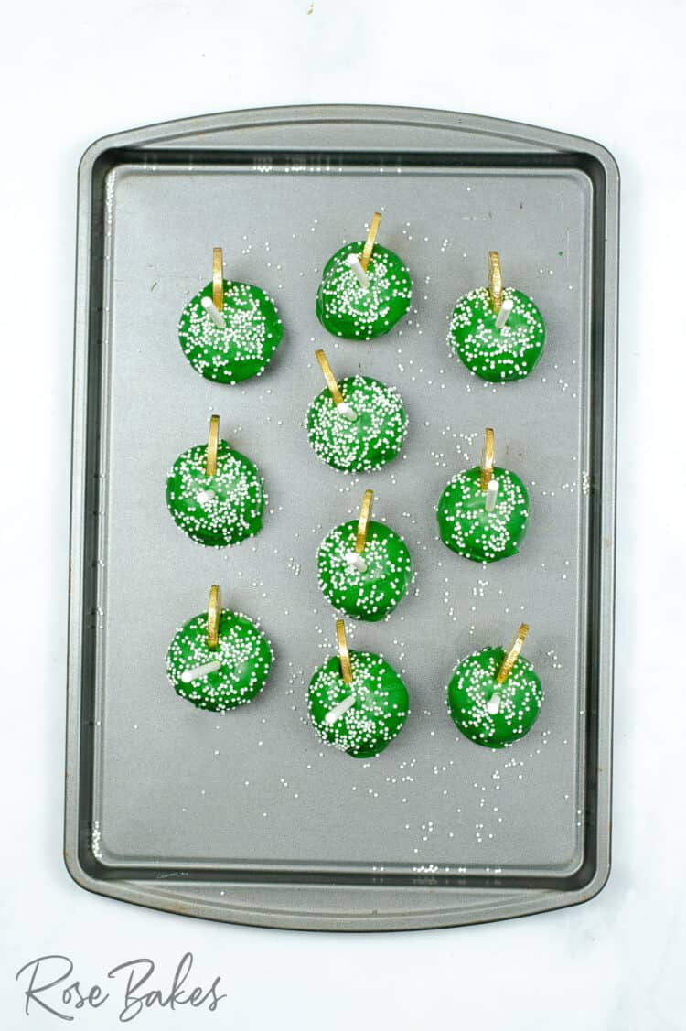 Top view of the finished green cake pops on a baking sheet.
