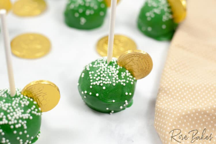 Green cake pops with white nonpareil sprinkles and a gold coins on top. Gold coins are sprinkled on the table among the cake pops.