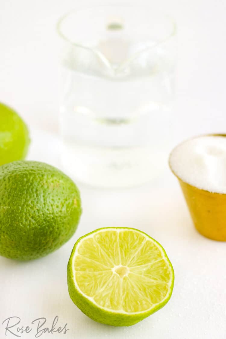 Whole limes, a lime sliced in half, a copper bowl of sugar, and clear pitcher of water.