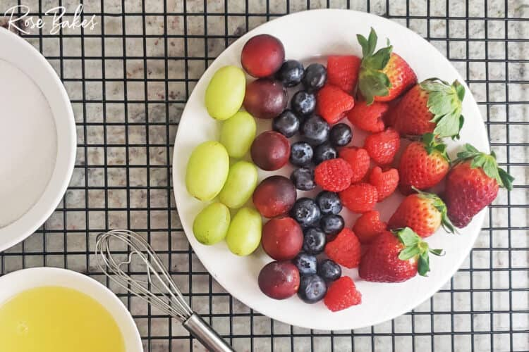 Overhead shot of a plate of green grapes, purple grapes, blueberries, raspberries, and strawberries