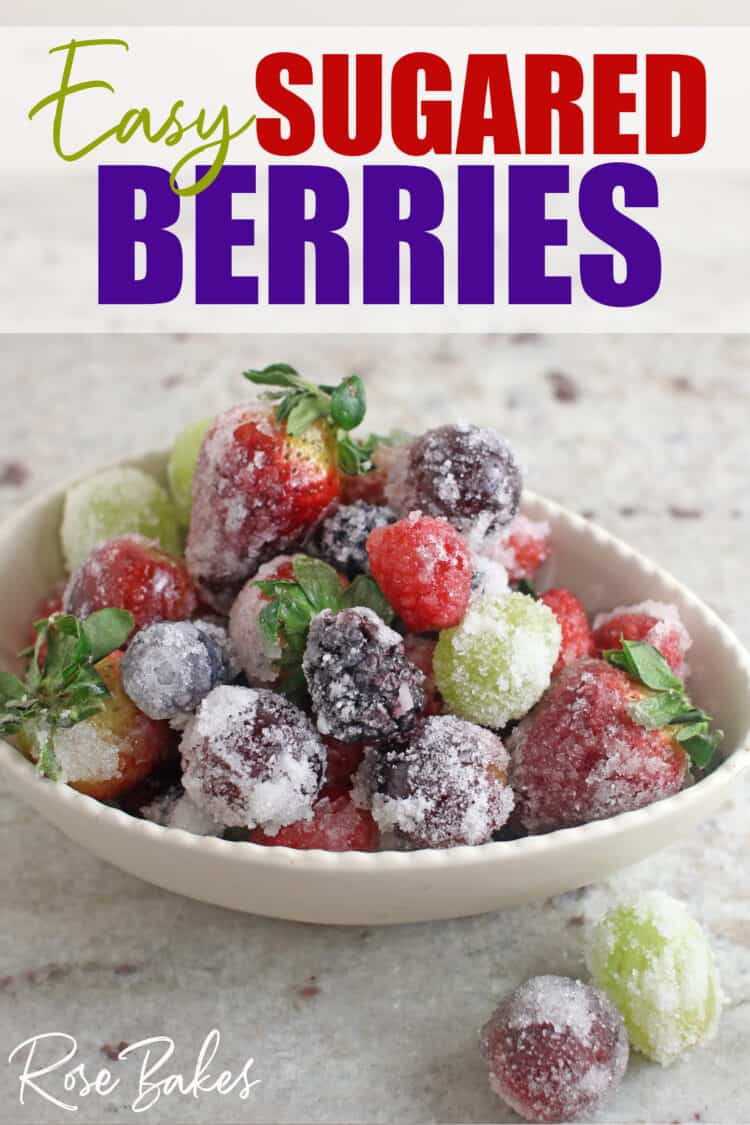 White bowl filled with sugared berries and grapes.