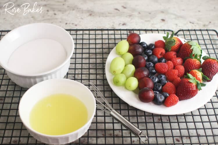 Ingredients for making sugared berries. Top left: bowl of sugar, bottom left: pasteurized egg whites and whisk, right: plate of green grapes, purple grapes, blueberries, raspberries, and strawberries