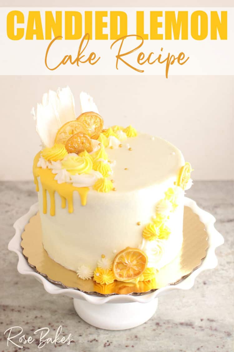 """Cake frosted in white buttercream with yellow drip and yellow buttercream rosettes and stars around the top left and front right of the cake.  Among the buttercream decorations are candied lemons and white chocolate fans.  The cake is displayed on a white cake stand with a large ruffled edge.  Text at the top of the image reads, """"Candied Lemon Cake Recipe"""""""