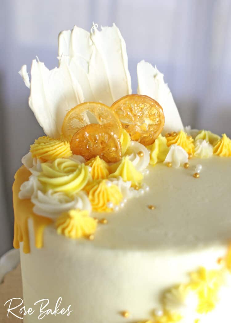 Close up of the yellow drip and yellow buttercream rosettes and stars on the top of the cake.  Among the buttercream decorations are candied lemons, white chocolate fans, and gold and white sugar pearls.