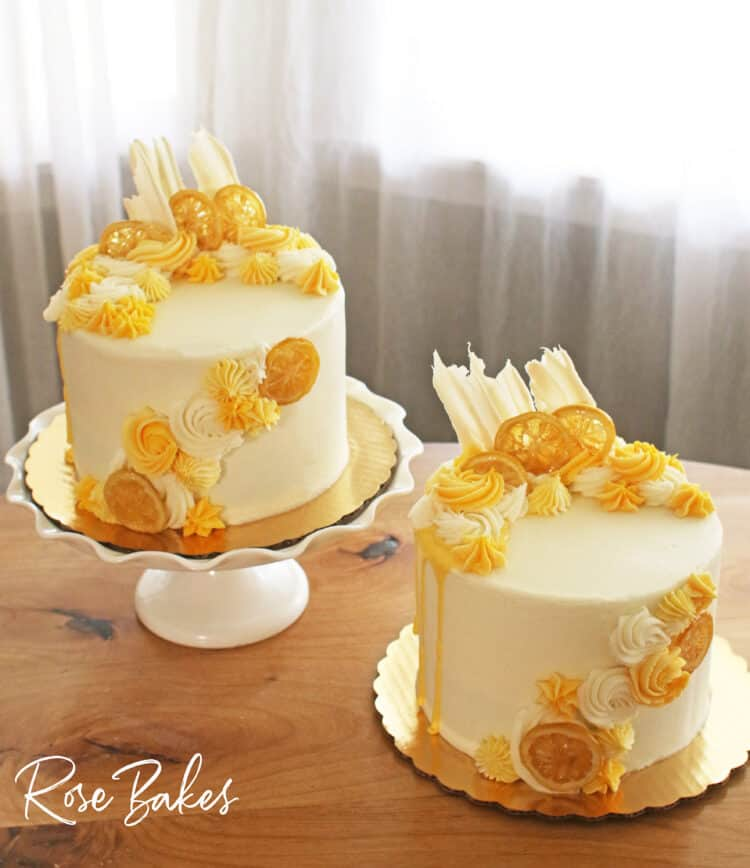 Two cakes frosted in white buttercream with yellow drip and yellow buttercream rosettes and stars around the top left and front right of the cake.  Among the buttercream decorations are candied lemons and white chocolate fans.  The cake on the left is displayed on a white cake stand with a large ruffled edge and the other is sitting on the wooden table.