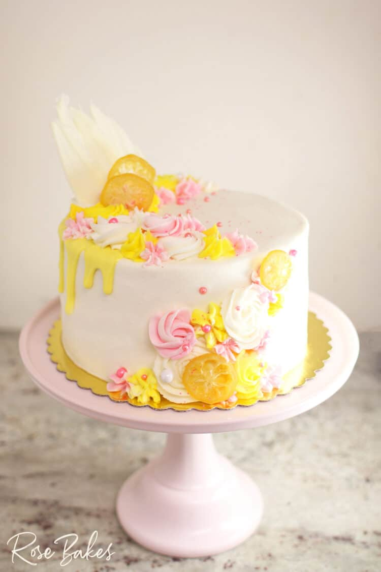 Cake frosted in white buttercream with yellow drip and yellow & pink buttercream rosettes and stars around the top left and front right of the cake.  Among the buttercream decorations are candied lemons, white chocolate fans, and pink sugar pearls.  The cake is displayed on a light pink cake stand
