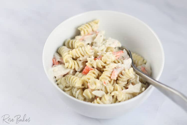 White bowl of imitation crab pasta salad made with rotini with a fork in it.