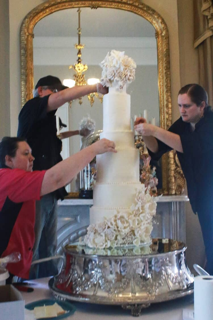 3 people working on placing flowers on 9 tier cake