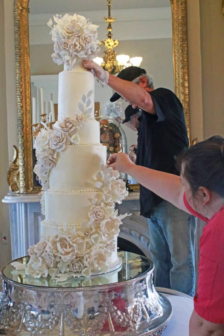 cake being held steady while being assembled by 3 people