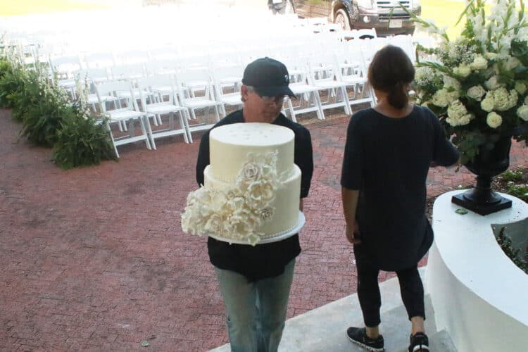 Man carrying 2 layers of wedding cake