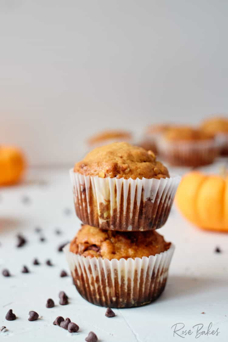 A couple of muffins stacked with chocolate chips scattered around on the table and mini orange pumpkins in the background.