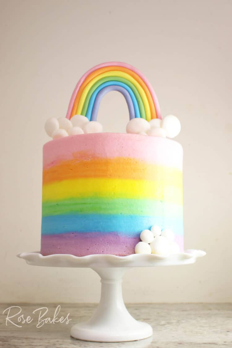 How to Smooth Frost a Cake and How to Get Sharp Buttercream Edges {Video Tutorial} - shown on a smooth-frosted buttercream rainbow cake on a white cake stand with fondant rainbow and clouds topper