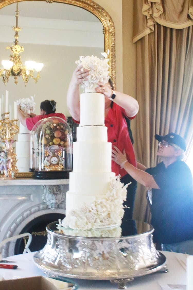 Very top tier being placed on cake by 2 people