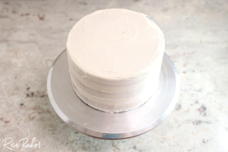 crumb coated  buttercream 1 tier cake on silver cake stand
