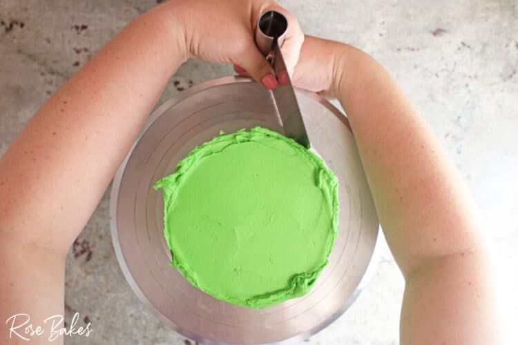 green icing being added to bottom tier on turntable