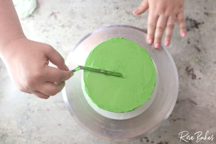 green buttercream icing being smoothed on cake tier with spatula not yet sharp edge