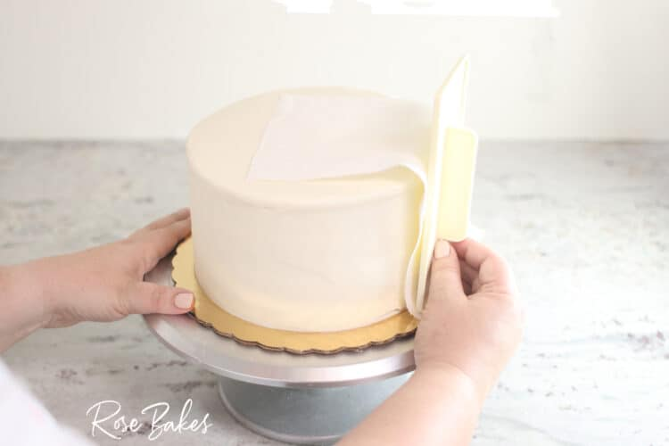 viva towel being used to smooth sides of buttercream icing cake