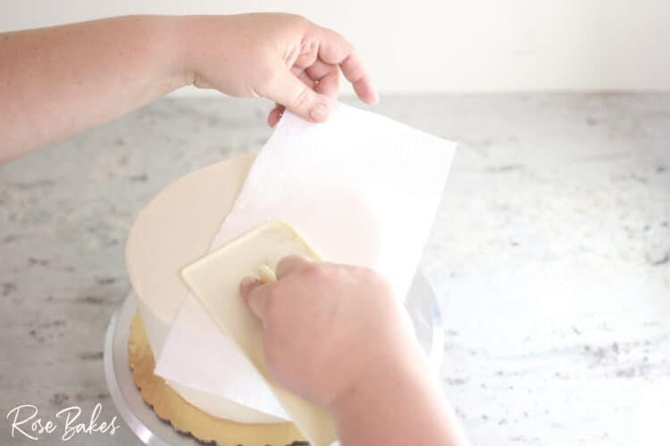 viva towel smoothing top of buttercream icing cake to create smooth seamless look
