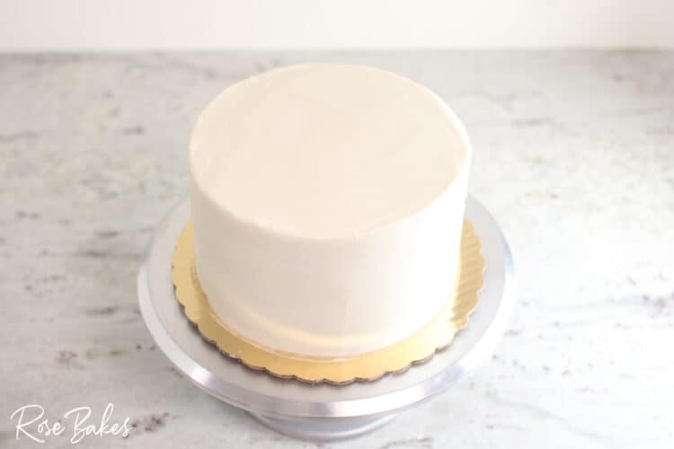 bottom tier of buttercream icing cake smoothed and on cake stand sharp edge