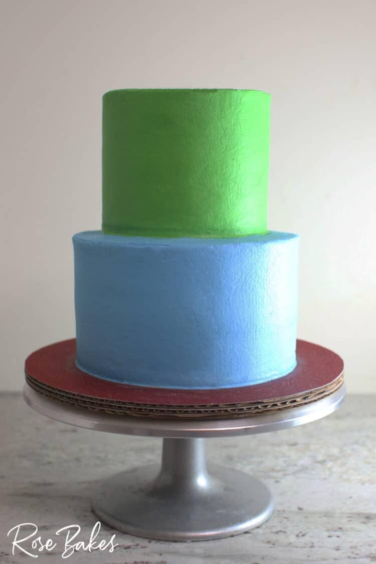 2 tier buttercream icing cake bottom tier deep sky blue top tier grass green with sharp edge