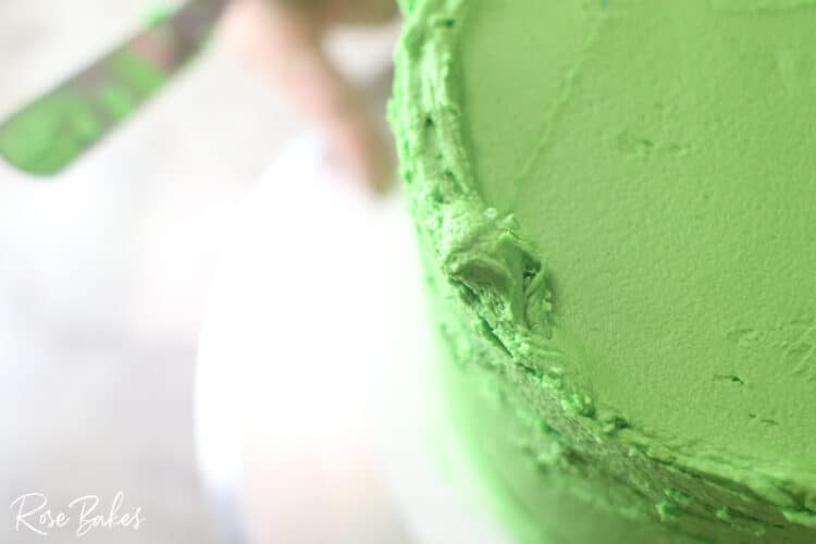 up close look at edges of green icing not yet smooth for sharp edge look