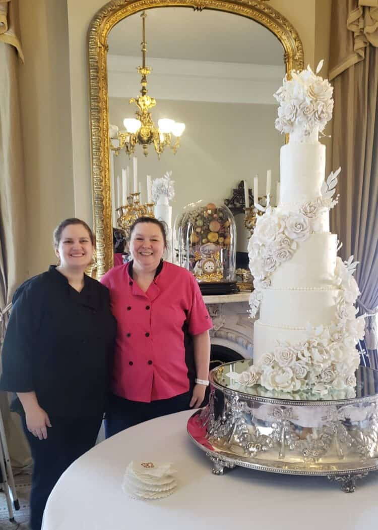 9 tier tall elegant luxury wedding cake with sugar flowers and Rose Atwater baker standing next to