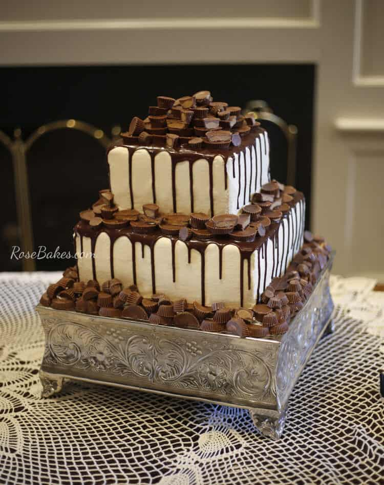 2 tier grooms cake white with chocolate drizzle and reeses peanut butter cups as topper and decor